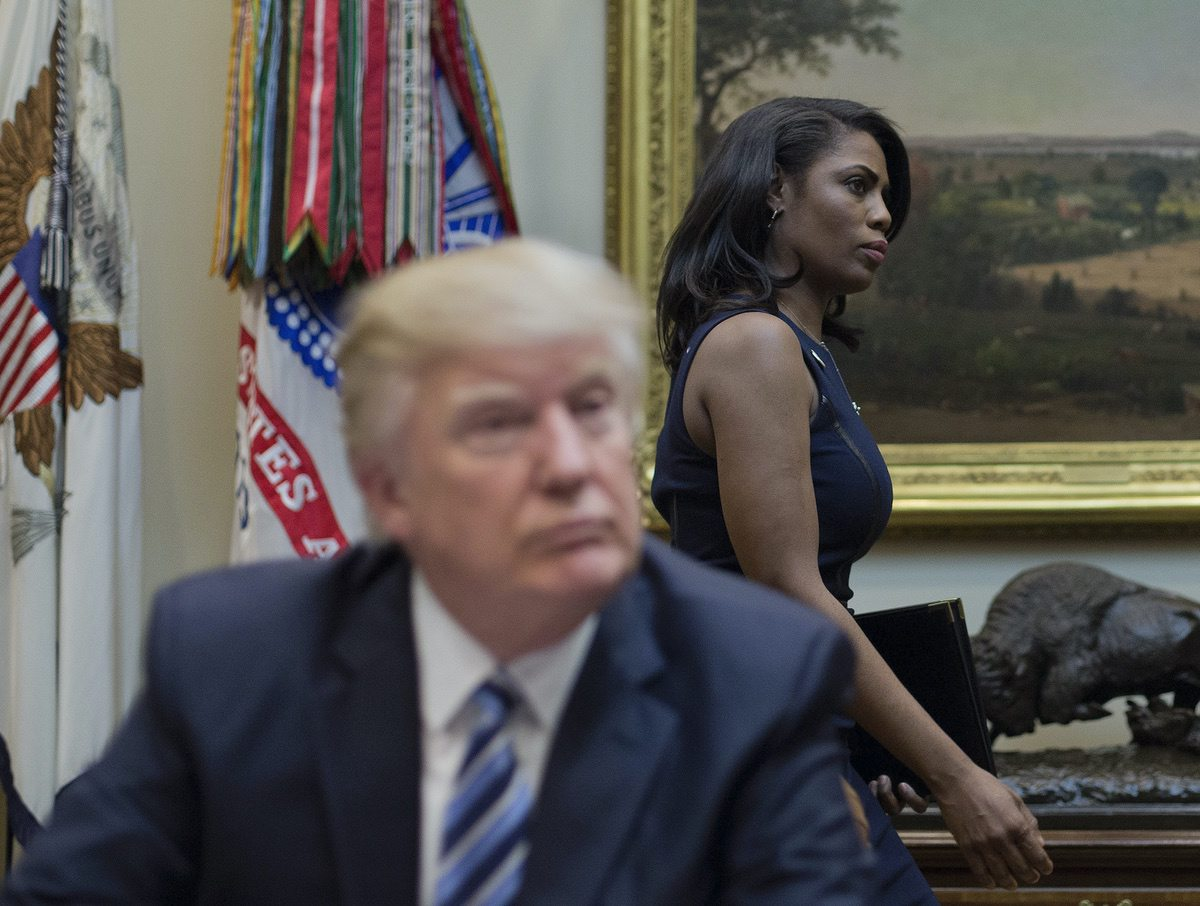 Omarosa Manigault, right, walks past President Donald Trump during a meeting on healthcare in the Roosevelt Room of the White House in Washington, Monday, March 13, 2017. (AP Photo/Pablo Martinez Monsivais)